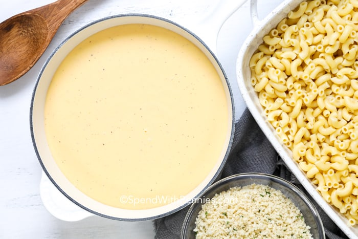 Cheese sauce next to breadcrumb topping and noodles for mac and cheese.