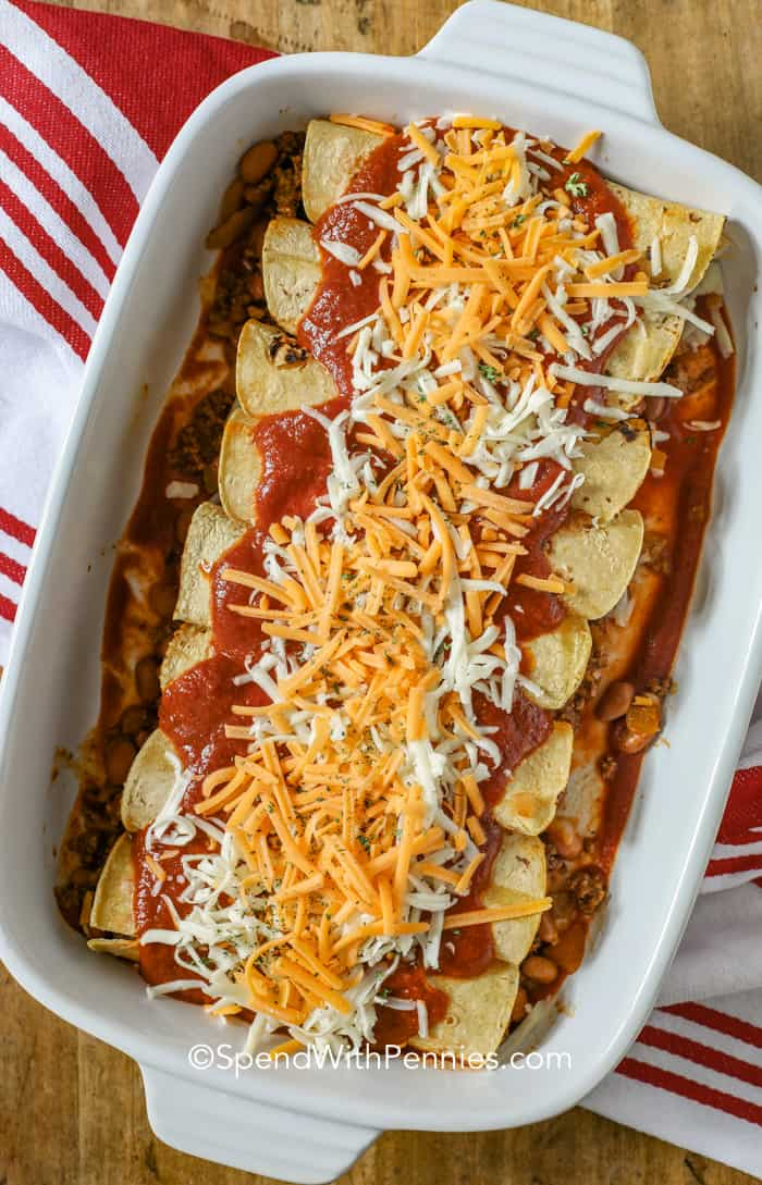 A casserole dish full of ground beef enchiladas topped with enchilada sauce and cheese.