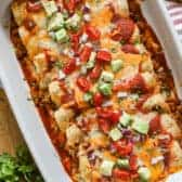 Ground Beef Enchiladas baked in a pan with toppings
