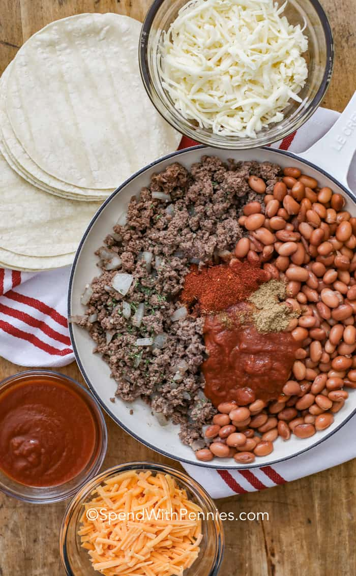 Ingredients for ground beef enchiladas in a pot surrounded by cheese, enchilada sauce, and tortillas.