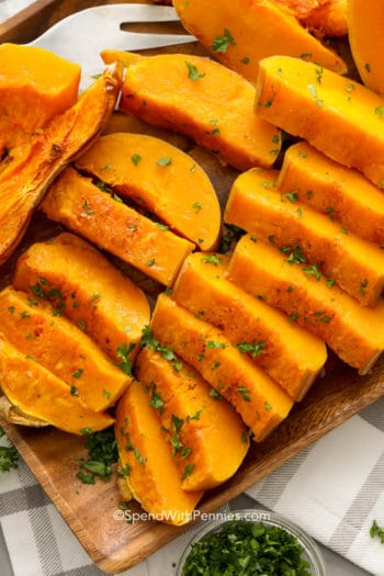 Butternut Squash sliced on a wood plate with parsley