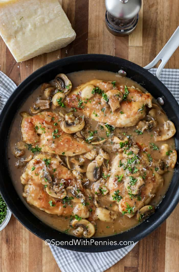 overhead of a pan of chicken marsala with mushrooms and marsala sauce, with parmesan cheese and a pepper grinder on the side