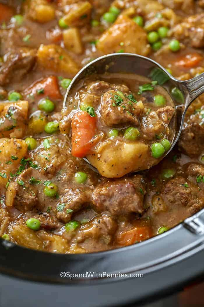 A ladle scooping crockpot beef stew to serve it.