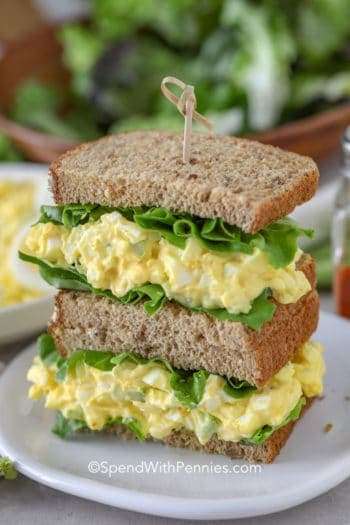 Egg salad sandwich on wheat bread on a white plate
