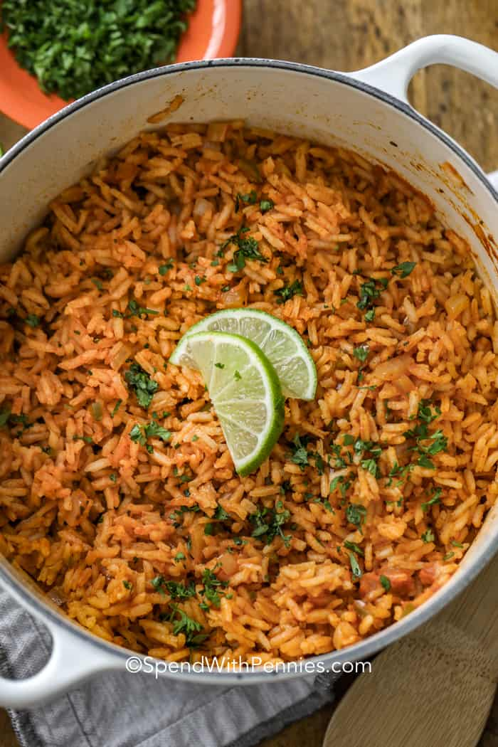 A pot of Mexican rice with limes and cilantro