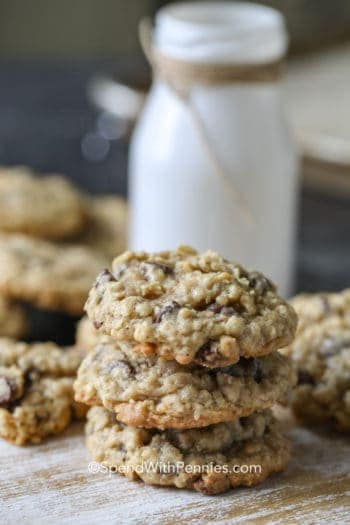 Stack of three Oatmeal Chocolate Chip Cookies with jar of milk in background