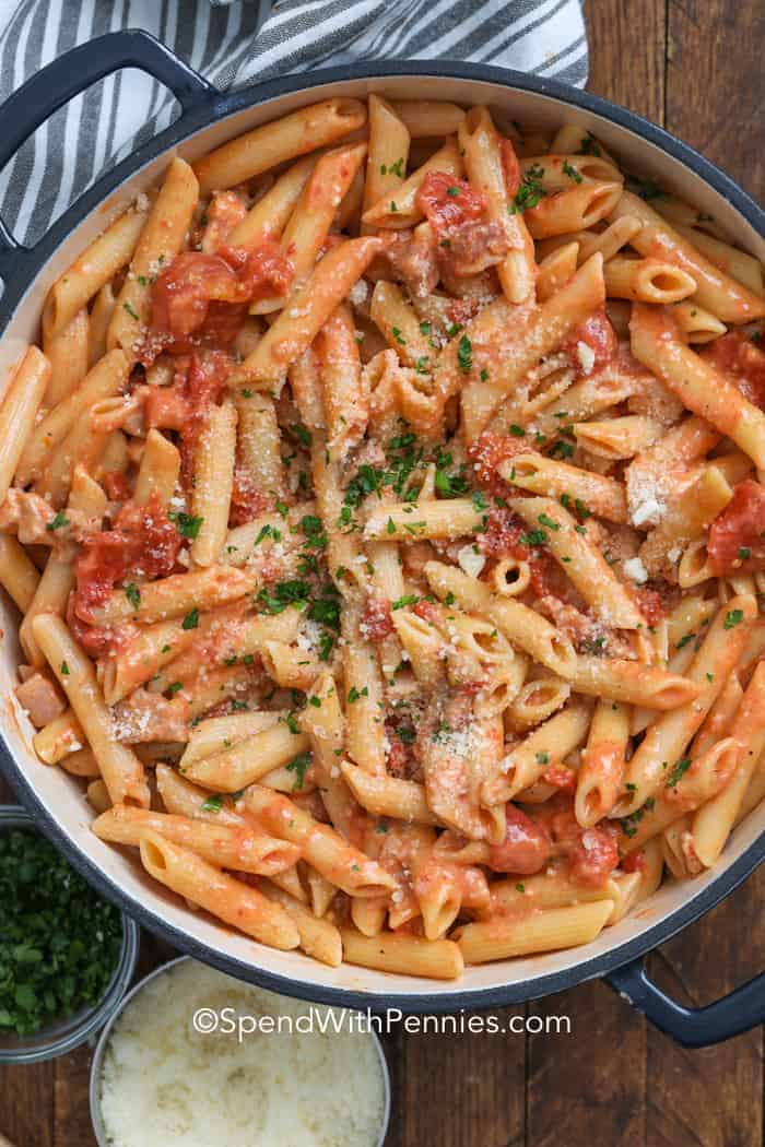 Penne alla Vodka garnished with parmesan and parsley in a large pot