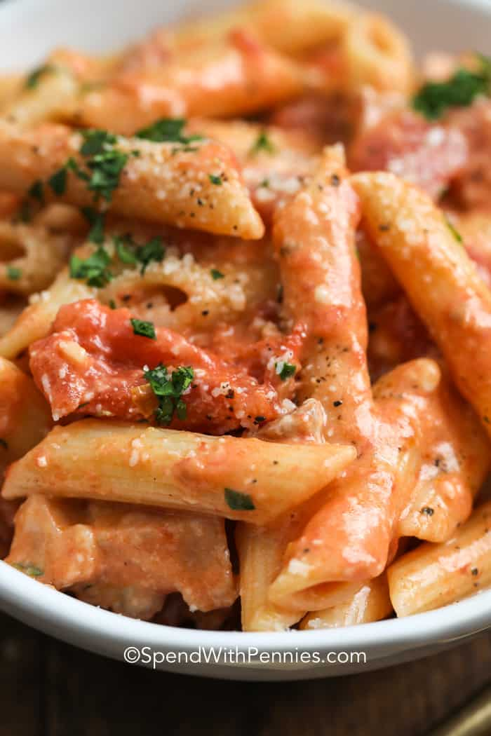 A photograph of penne alla vodka creamy tomato sauce in a bowl with parsley and parmesan cheese.