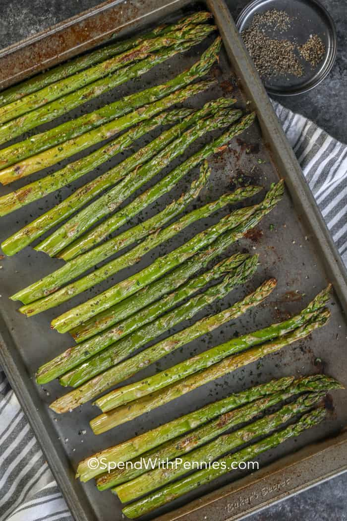 Asparagus spears on a baking sheet.