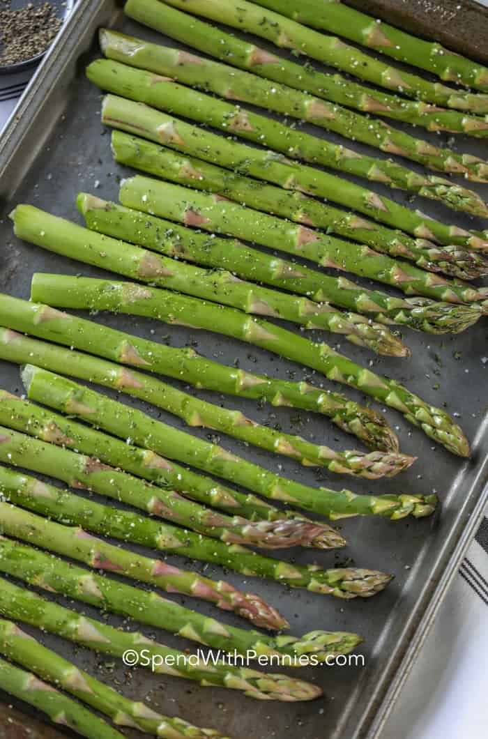 Uncooked asparagus on a baking sheet.