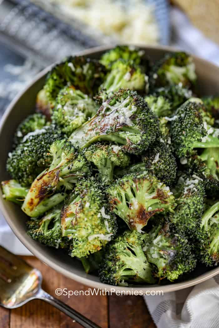 Roasted broccoli in a fret serving bowl topped with parmesan cheese.
