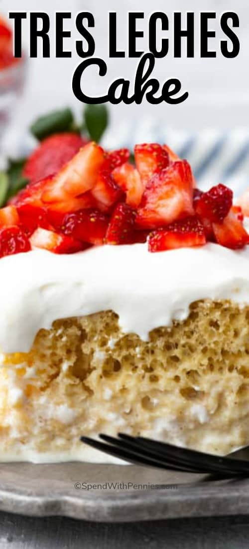 Tres Leches Cake on a plate with strawberries and a fork with writing