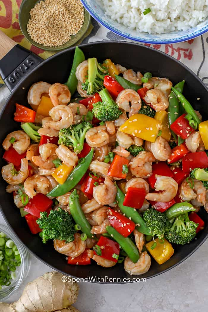 A frying pan full of shrimp stir fry surrounded by rice, sesame seeds, and ginger.