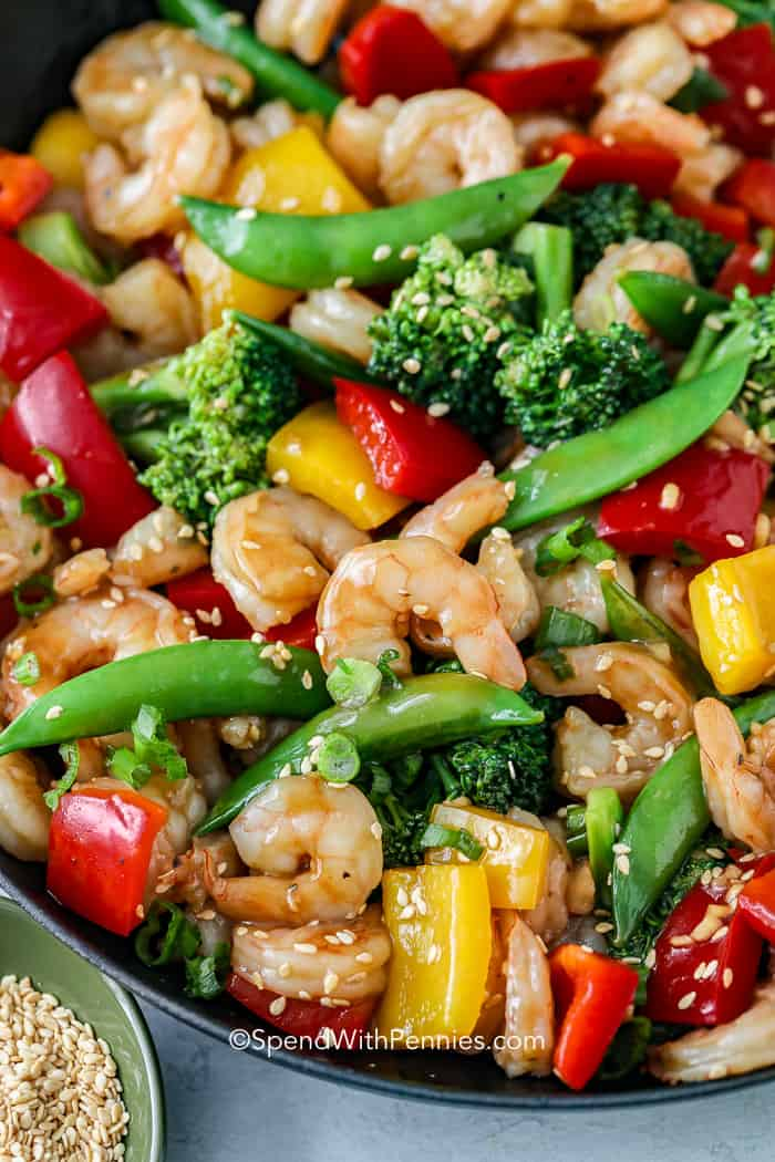 A close up of shrimp stir fry full of shrimp, peas, peppers, and broccoli.
