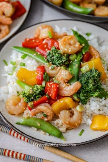 Shrimp stir fry on a bed of rice garnished with sesame seeds and green onions
