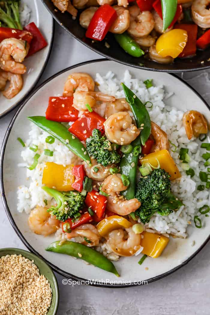 An overhead shot of shrimp stir fry on a bed of rice on a white plate.