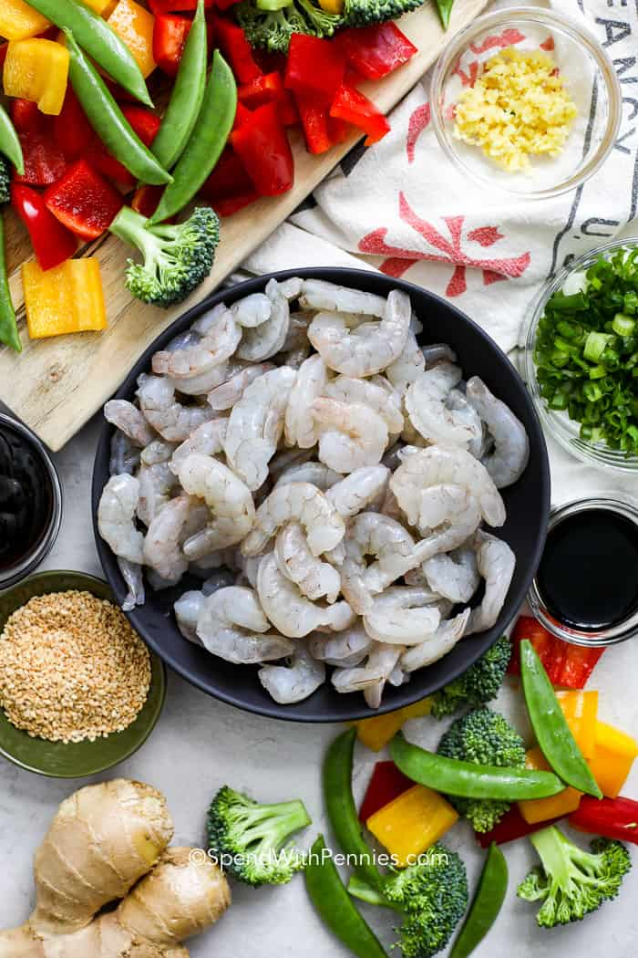 Shrimp stir fry ingredients like raw shrimp, veggies, ginger, and garlic.
