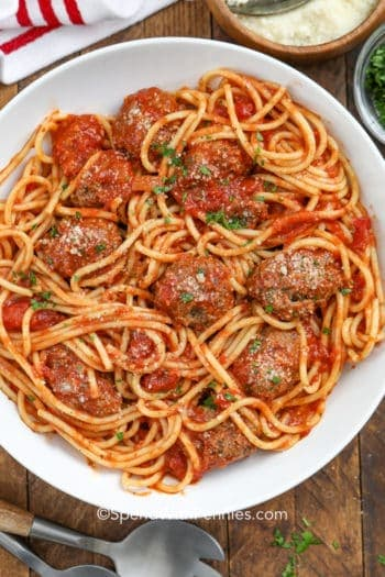 A plate of spaghetti and meatballs topped with parsley and parmesan cheese