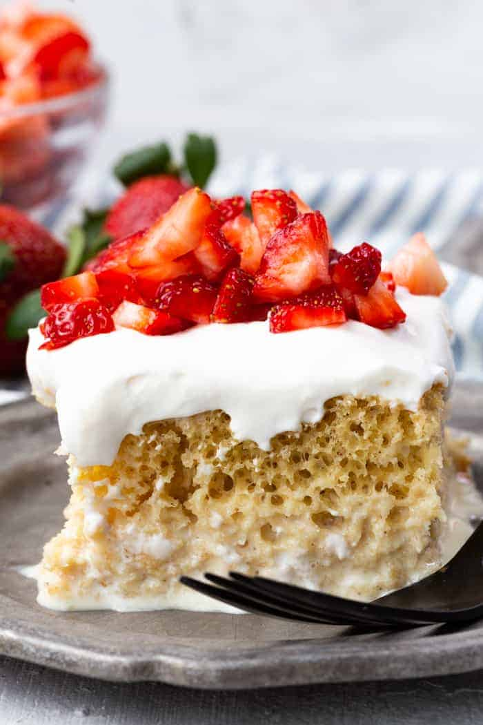 A slice of tres leches cake on a pewter plate, cake is topped with strawberries