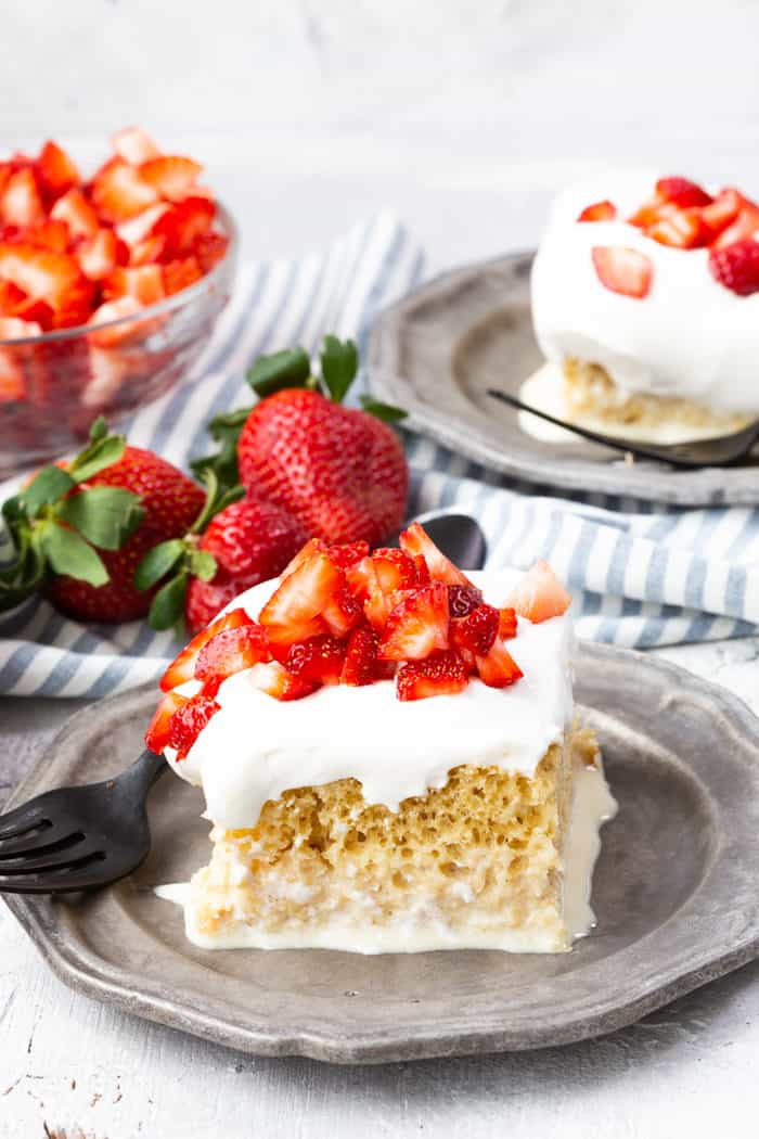 Tres leches cake with strawberries on plates