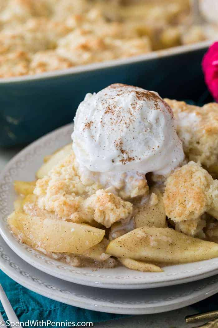 Apple cobbler topped with ice cream on white plate with a dish of apple cobbler in the background