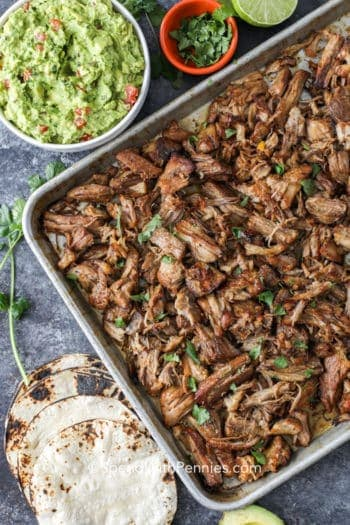 Overhead shot of Pork Carnitas on a baking sheet surrounded by tortillas, limes and avocado