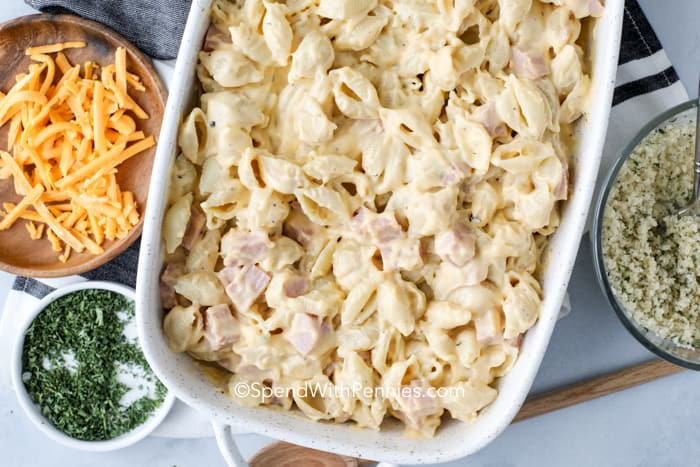 Overview of the ham,pasta and cheese sauce mixture in a white casserole dish with the remaining toppings on the side.