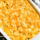 Cheesy Potatoes in a white casserole dish with parsley