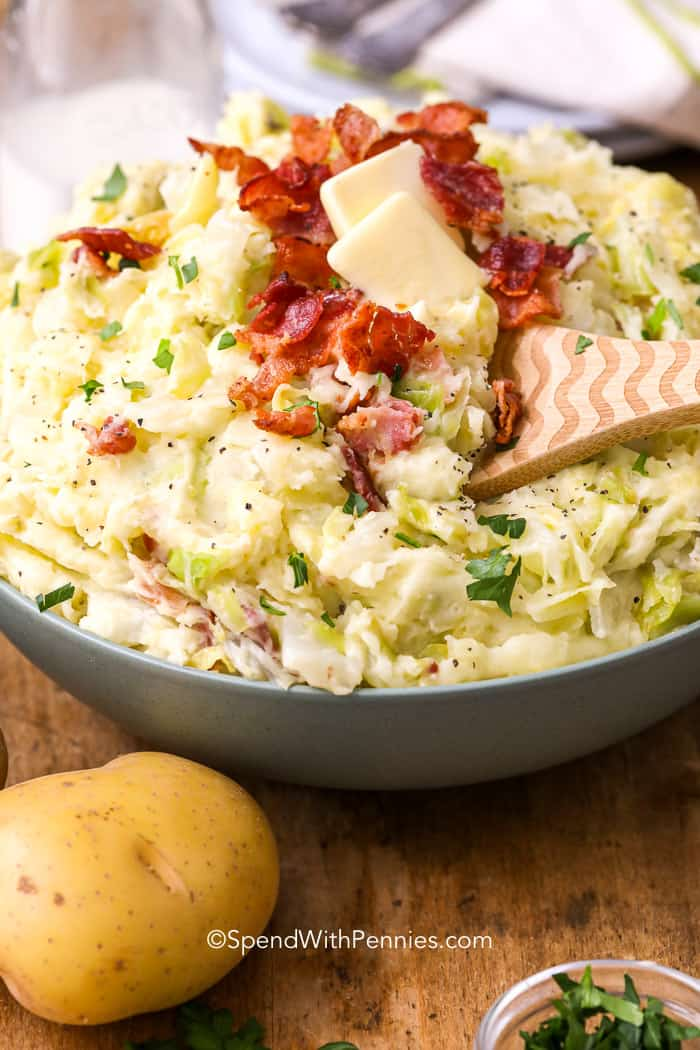 colcannon in a bowl with pats of butter, crispy bacon and parsley