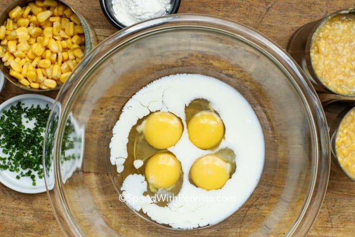 Eggs and milk in a bowl with other ingredients on the side for corn pudding