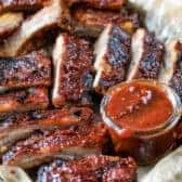 Crock Pot Ribs on a baking sheet with dipping sauce