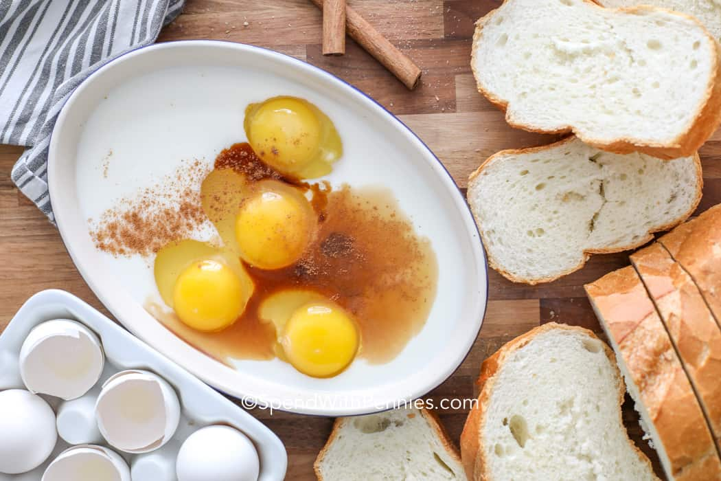 Eggs, milk and cinnamon in a bowl surrounded by bread and eggs