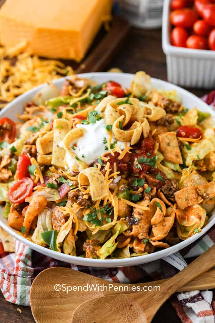 A fully prepared Frito taco salad topped with extra corn chips and shredded cheese.