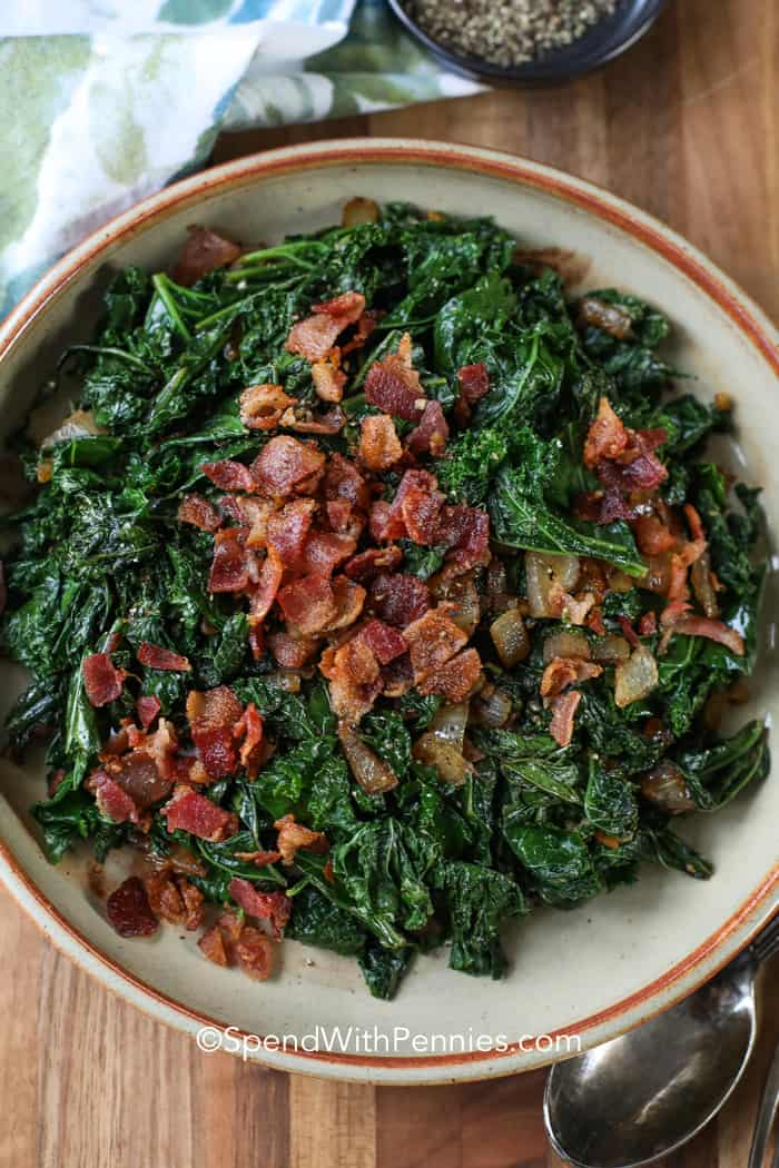 A bowl of sauteed kale topped with crispy bacon