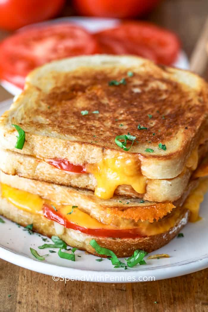 2 grilled cheese sandwiches stacked on a plate.