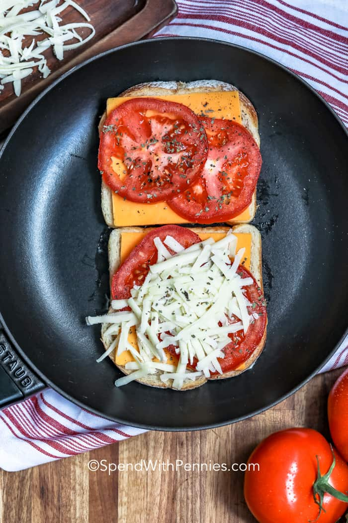 Bread topped with cheese and tomatoes, open faced on a frying pan.
