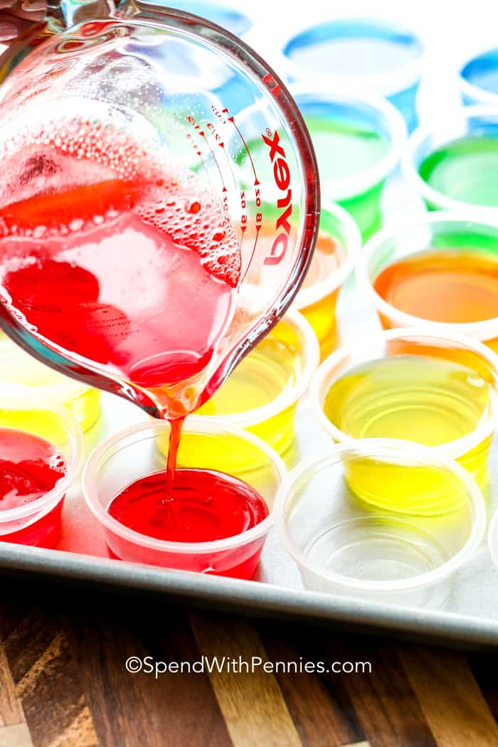 Jello shots lined up on a baking tray with the jello mixture being poured into them.