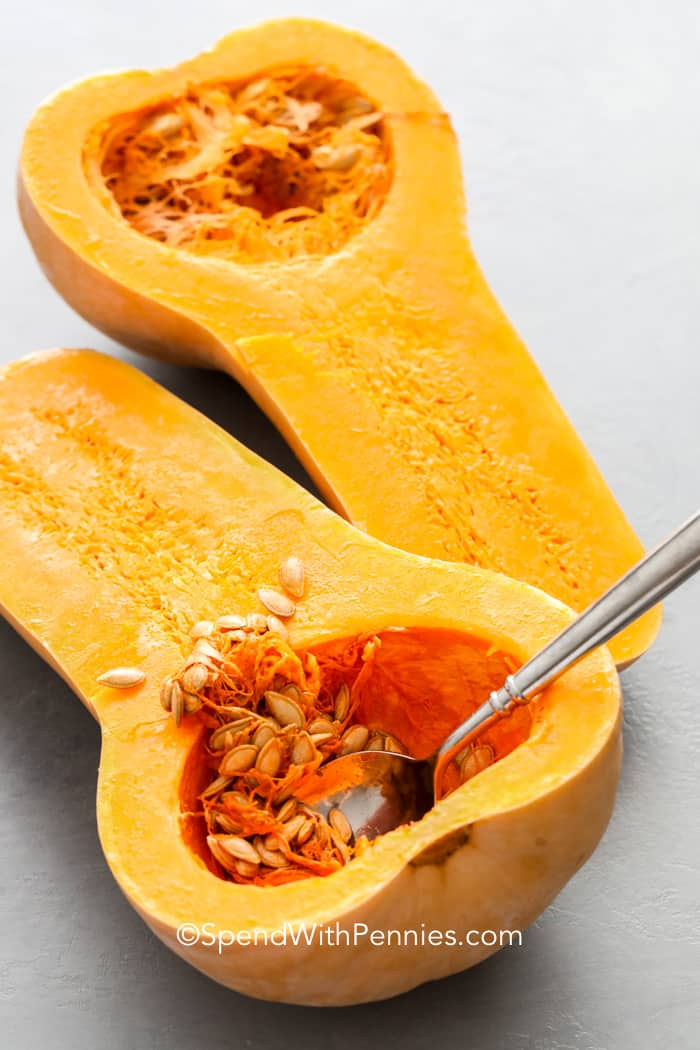Two halves of butternut squash, removing seeds with a spoon