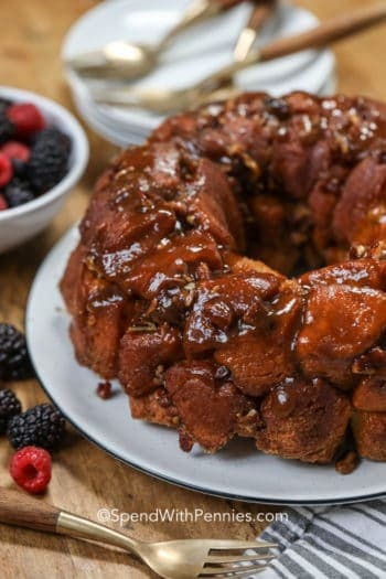 Monkey bread on a plate with berries in the background