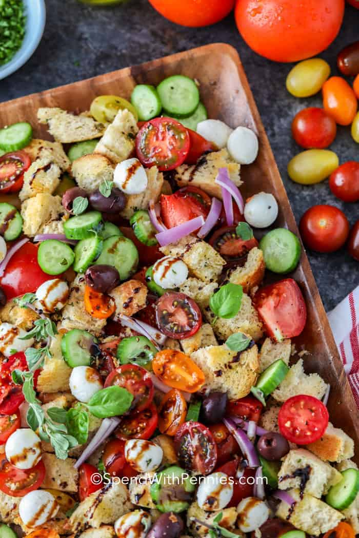 A close up of a wooden tray full of Panzanella Salad, drizzled with balsamic vinaigrette and garnished with basil.
