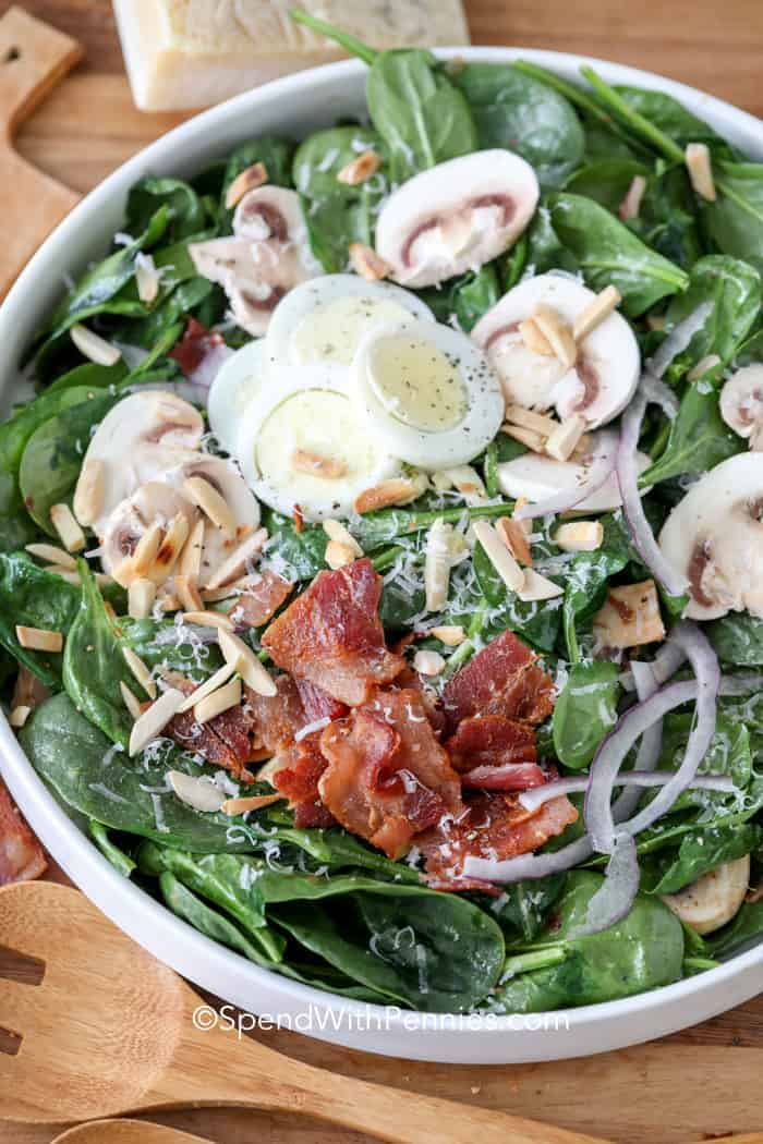 A prepared spinach salad with all the toppings in a white bowl.