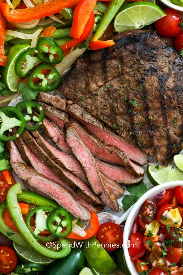 Sliced flank steak with peppers, onions and tomatoes for making grilled fajitas