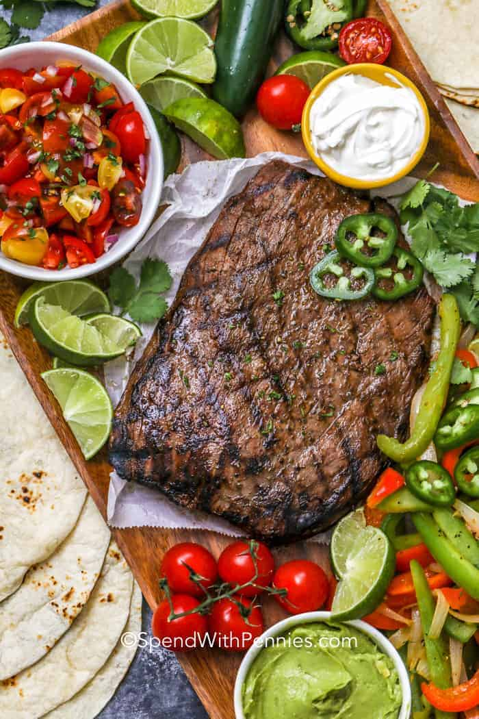 Grilled flank steak fajitas on a board with toppings