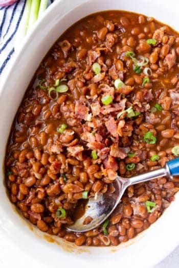 Baked Beans with a spoon garnished with green onions and bacon