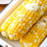 Baked Corn on the Cob in a dish with butter and salt and pepper