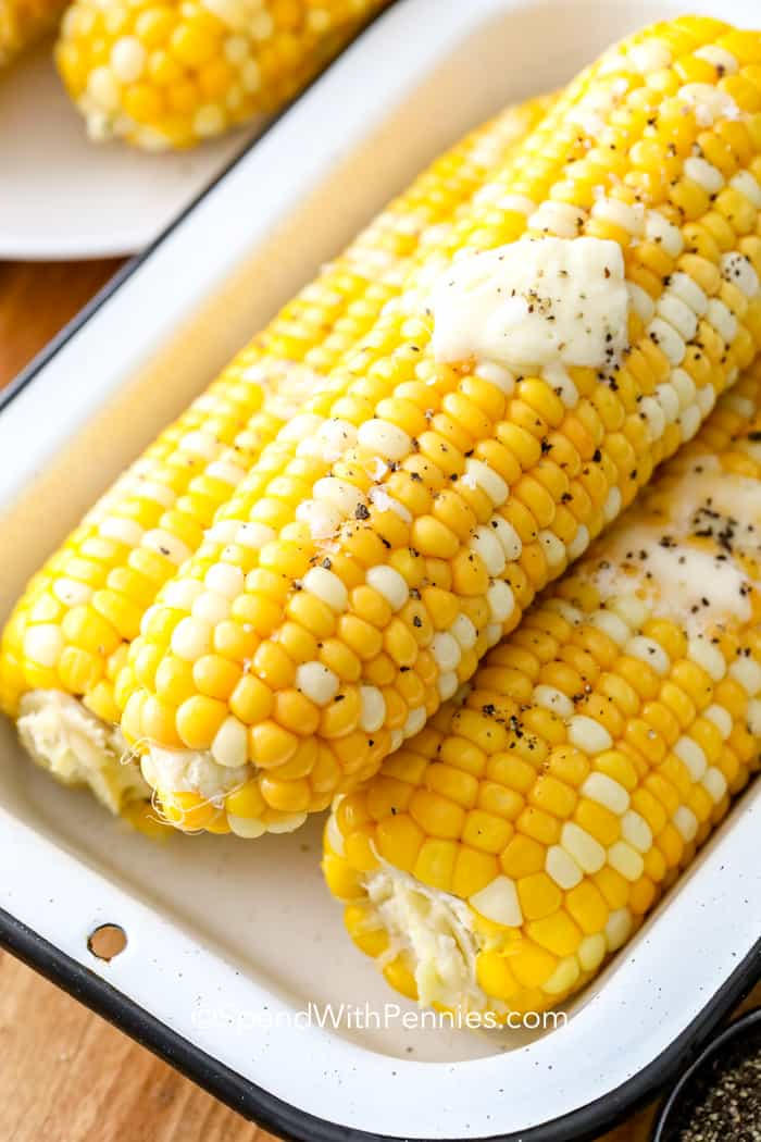 Baked corn on the cob stacked in a serving dish with a pat of butter on top.