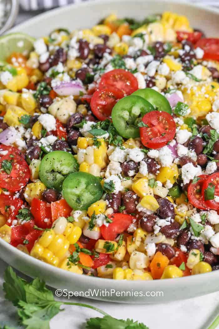 Close up of a black bean corn salad garnished with jalapeños, cherry tomatoes, and cilantro.