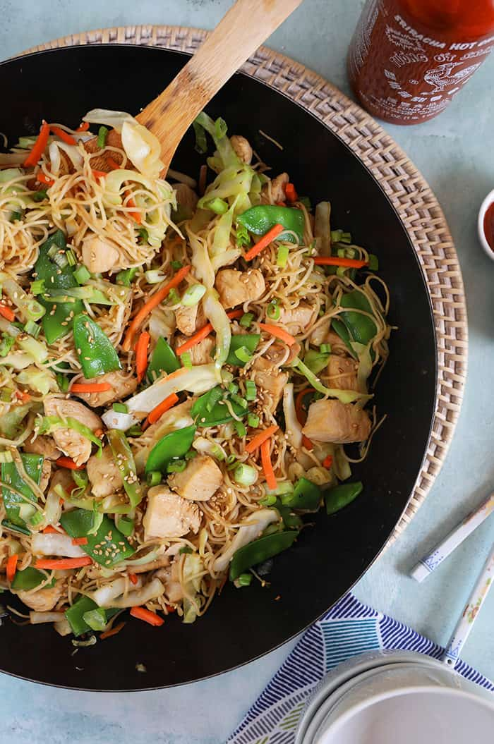 Chicken chow mein in a bowl with a wooden spoon