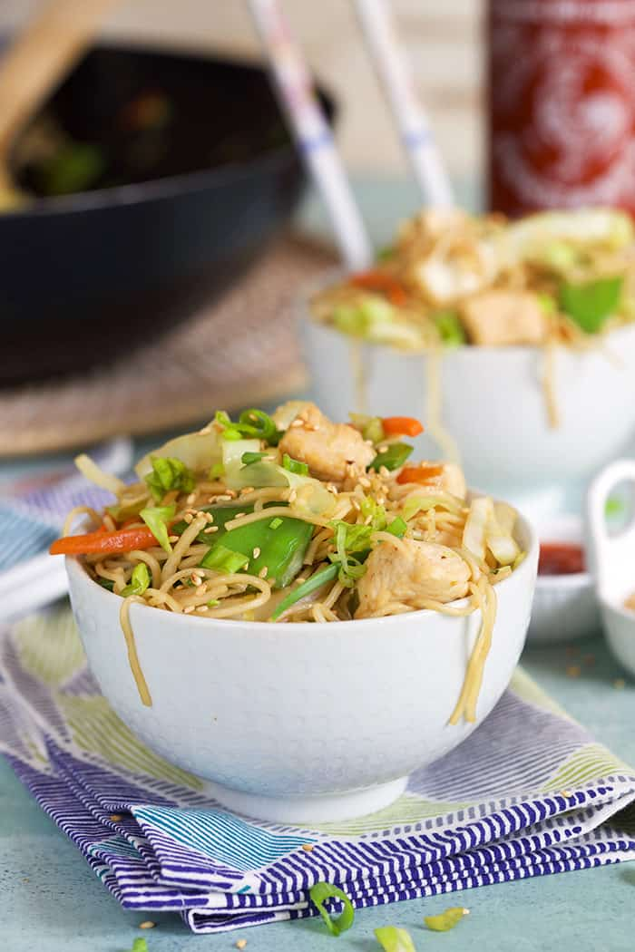 Chicken chow mein in a white bowl with sesame seeds and green onions