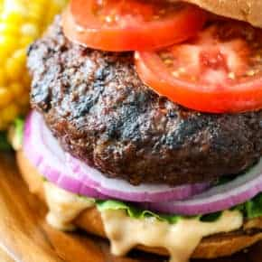 Classic hamburger on a wooden plate with tomatoes onions lettuce and sauce